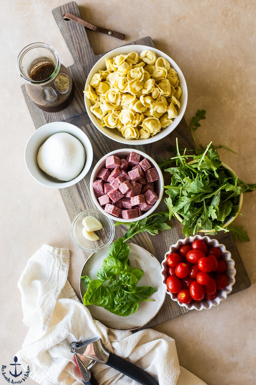 Overhead photo of ingredients for Tortellini, Roasted Tomato and Salami Salad in dividual bowls