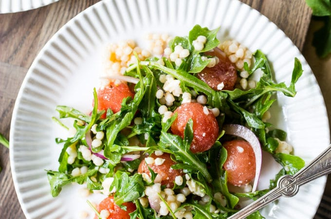 Overhead photo of watermelon, feta and couscous salad with citrus vinaigrette on a white plate with a fork