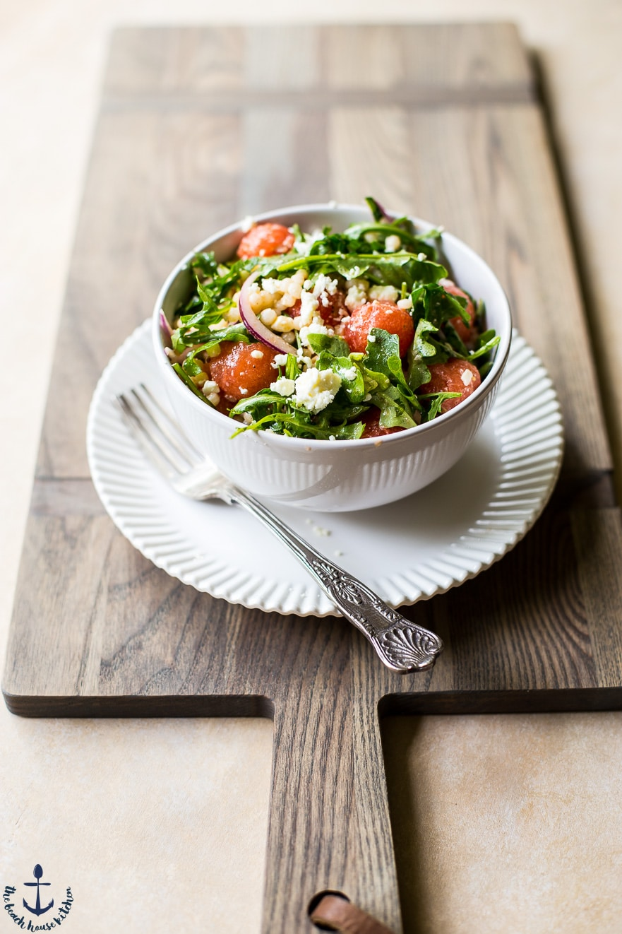 Watermelon, feta and couscous salad in a bowl on a white plate