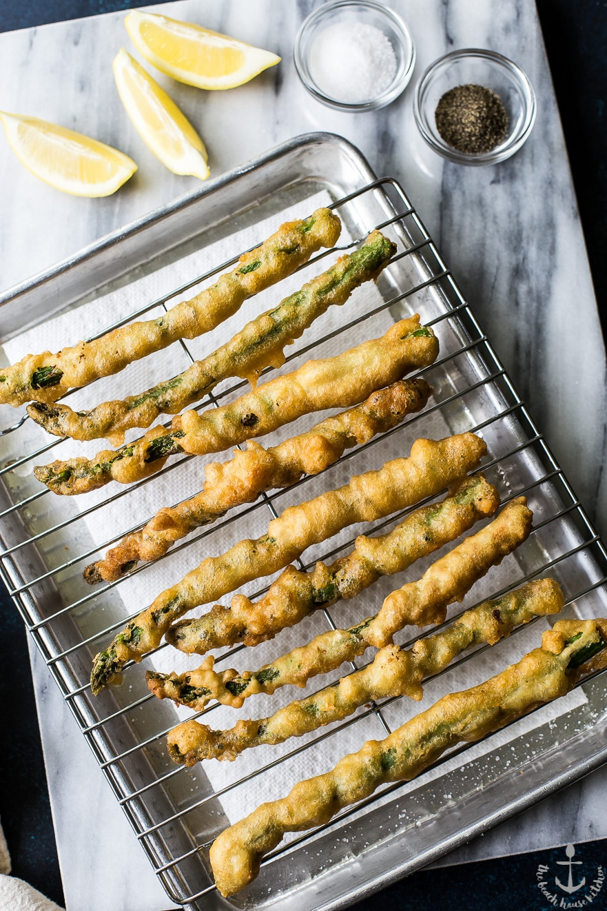 Overhead photo of asparagus tempura on a rack on a silver tray