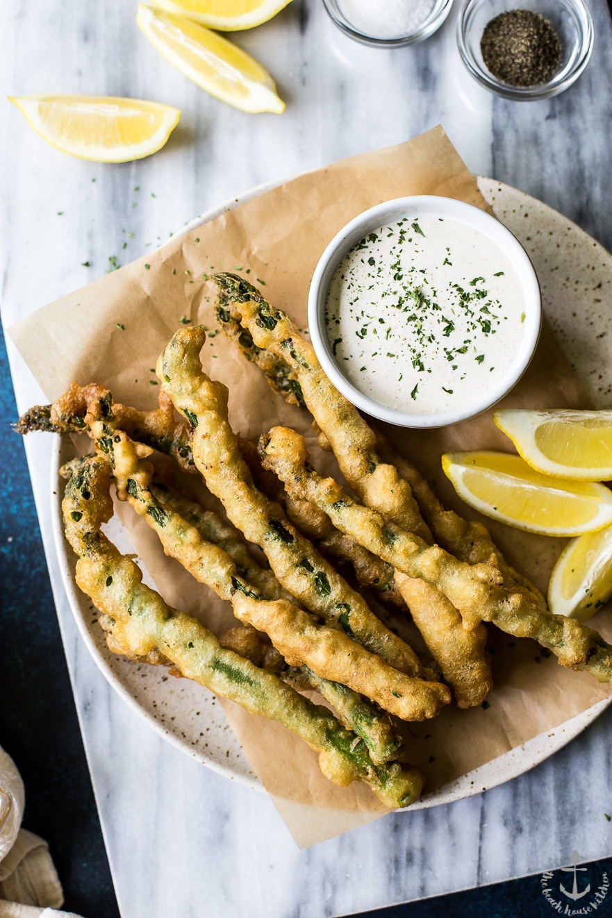 Overhead photo of asparagus tempura with horseradish cream sauce on a plate on a marble board