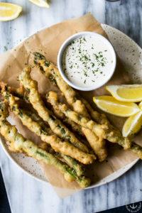 Overhead photo of asparagus tempura on a plate with horseradish cream sauce