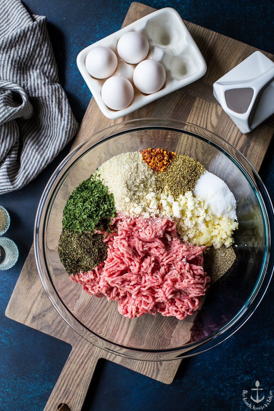 Overhead photo of ingredients for Greek meatballs in a glass bowl