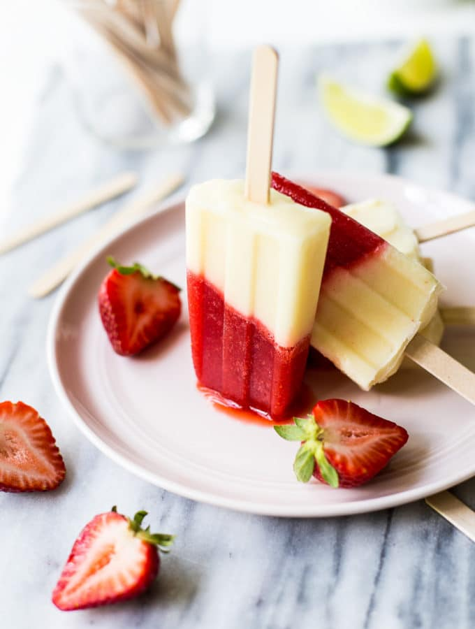 Miami Vice Boozy Popsicles on a pink plate surrounded by a few halved strawberries