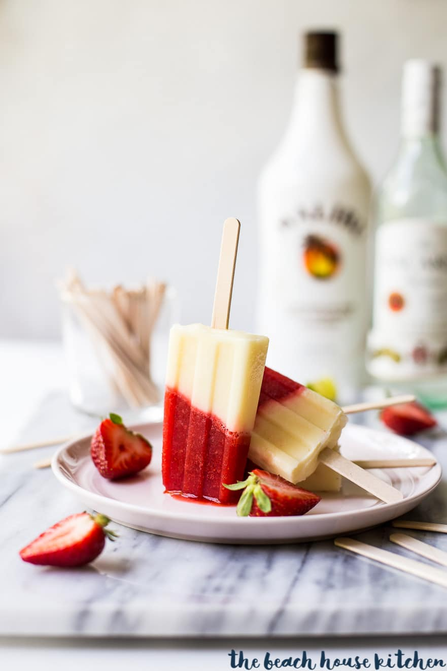 Miami Vice Boozy Popsicles on a pink plate surrounded by sliced strawberries
