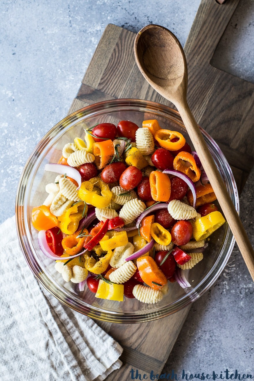 Overhead photo of veggies and gnocchi in a clear bowl with a wooden spoon