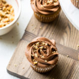 Overhead photo of banana cupcakes with chocolate buttercream on a wooden board