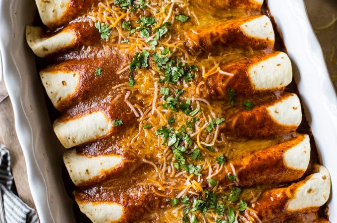 Overhead photo of Homemade Easy Beef Enchiladas in a long white dish with a few sides around it