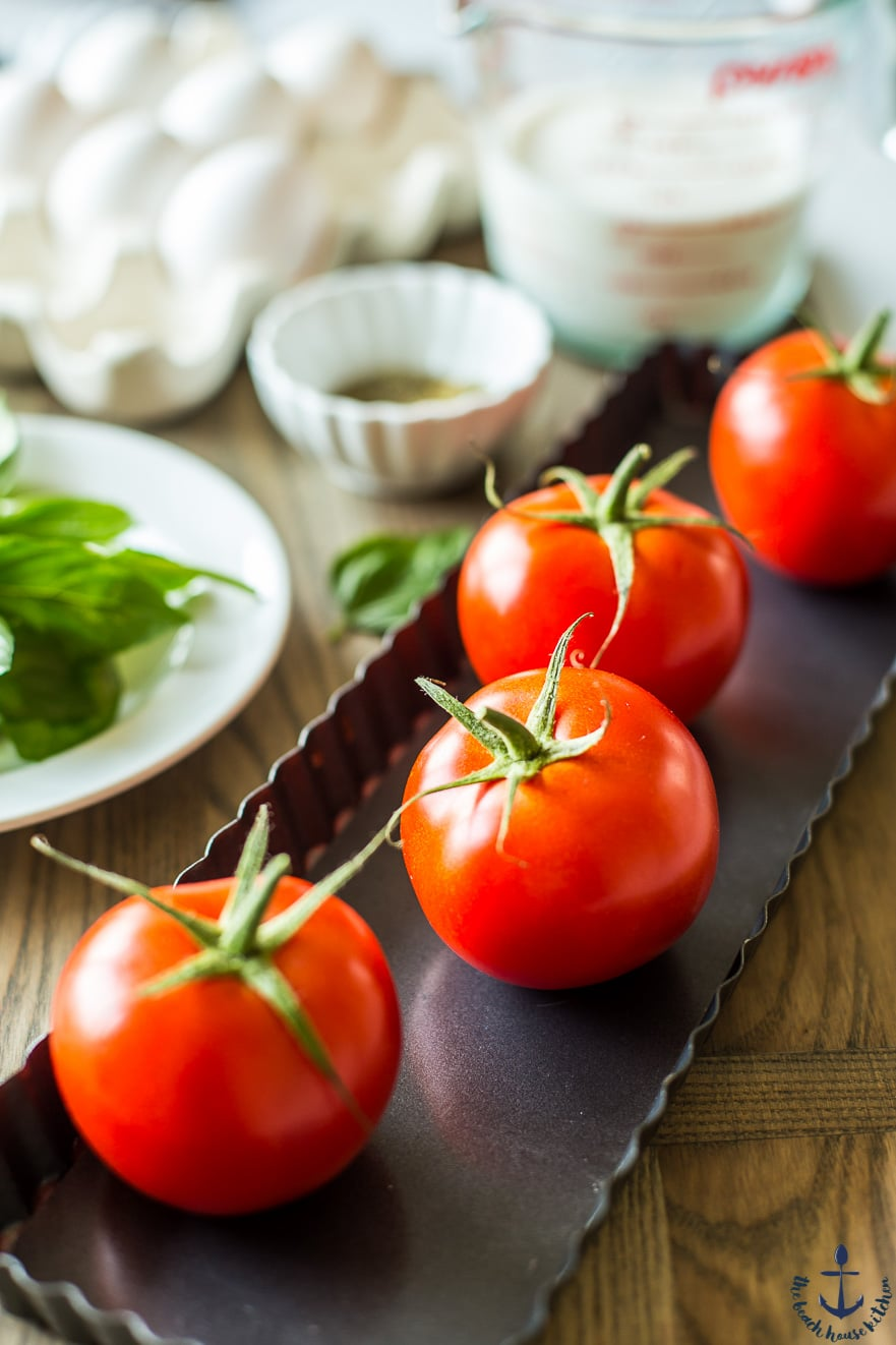 Four fresh tomatoes in a tart pan with eggs, herbs and other ingredients blurred in the background