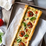 Overhead photo of tomato basil tart on a parchment lined baking sheet