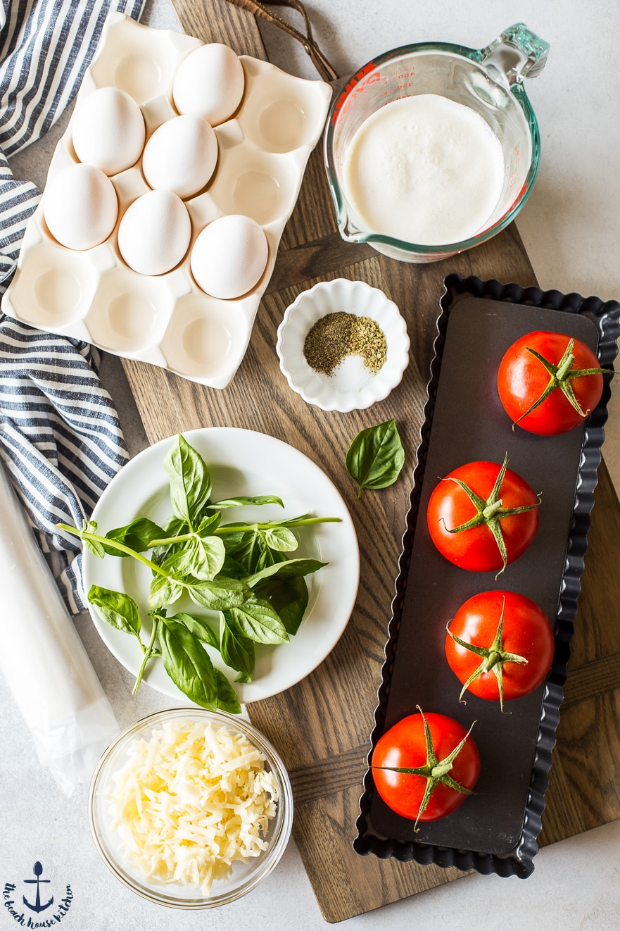 Overhead photo of ingredients for tomato basil tart on a wooden board