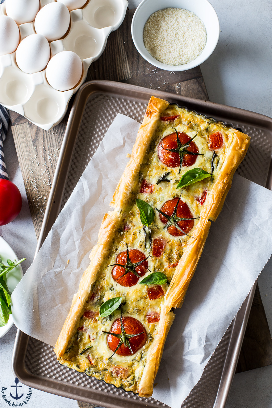 Overhead photo of tomato basil tart on parchment lined baking sheet
