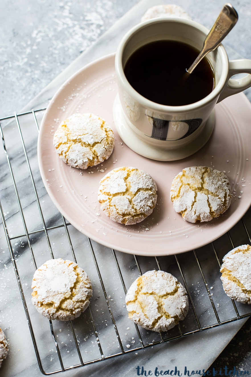 Overhead photo of amaretti cookies on a plate with a cup of coffee