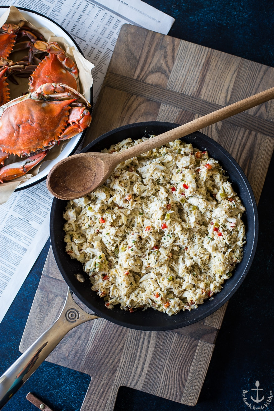 Overhead photo of deviled crab in skillet with wooden spoon