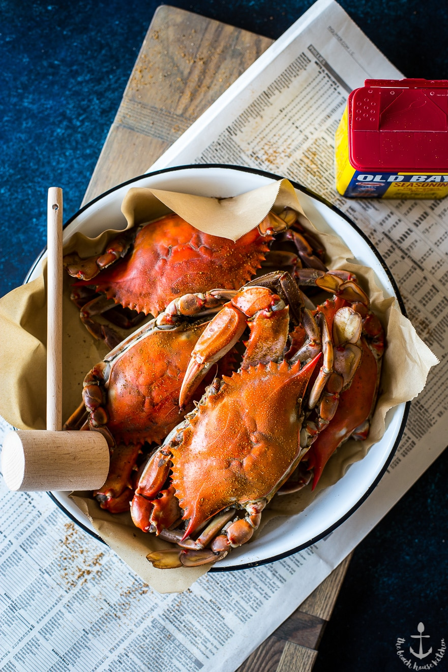 Overhead photo of cooked crabs in white enamel dish with wooden hammer