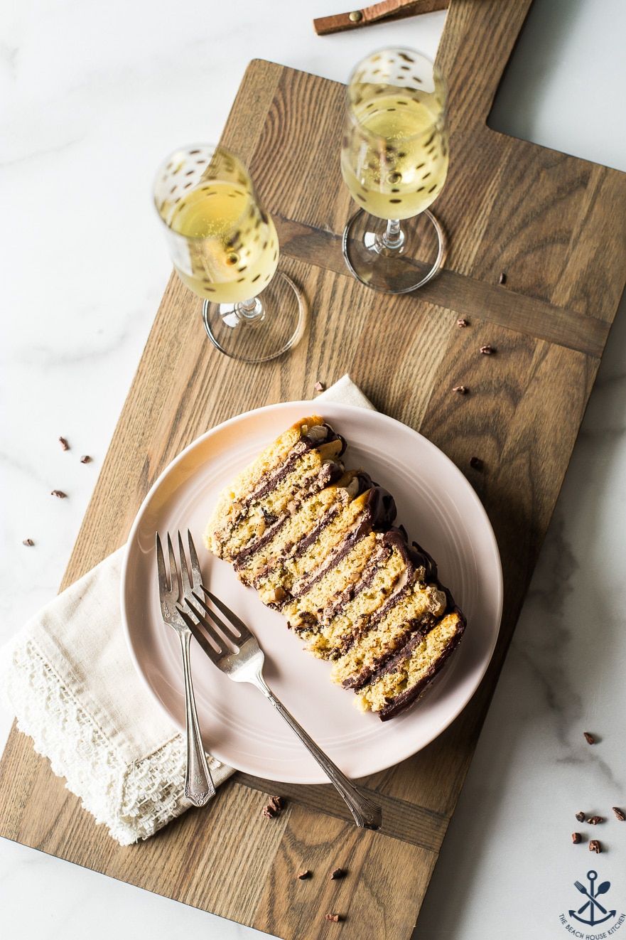Overhead photo of a slice of Armenian-style layer cake on a plate with two glasses of champagne