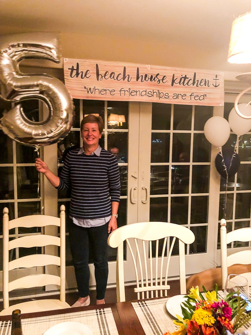 Mary Ann from the beach house kitchen holding a silver five balloon