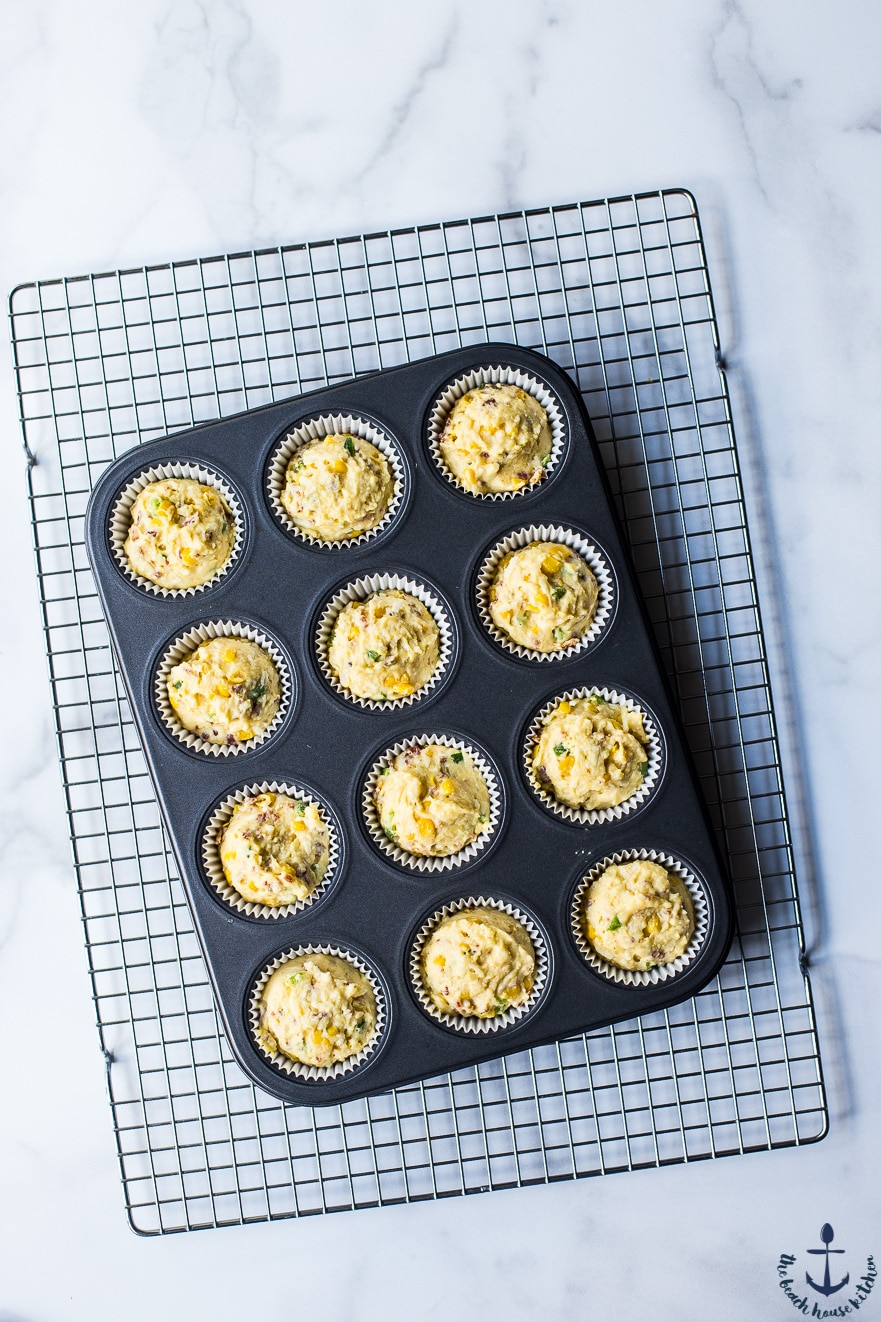 Overhead photo of prebaked chaddar jalapeno bacon corn muffins in muffin pan on wire rack