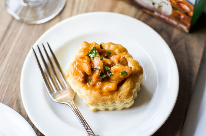 A shrimp etouffee vol au vent on a white plate with a fork