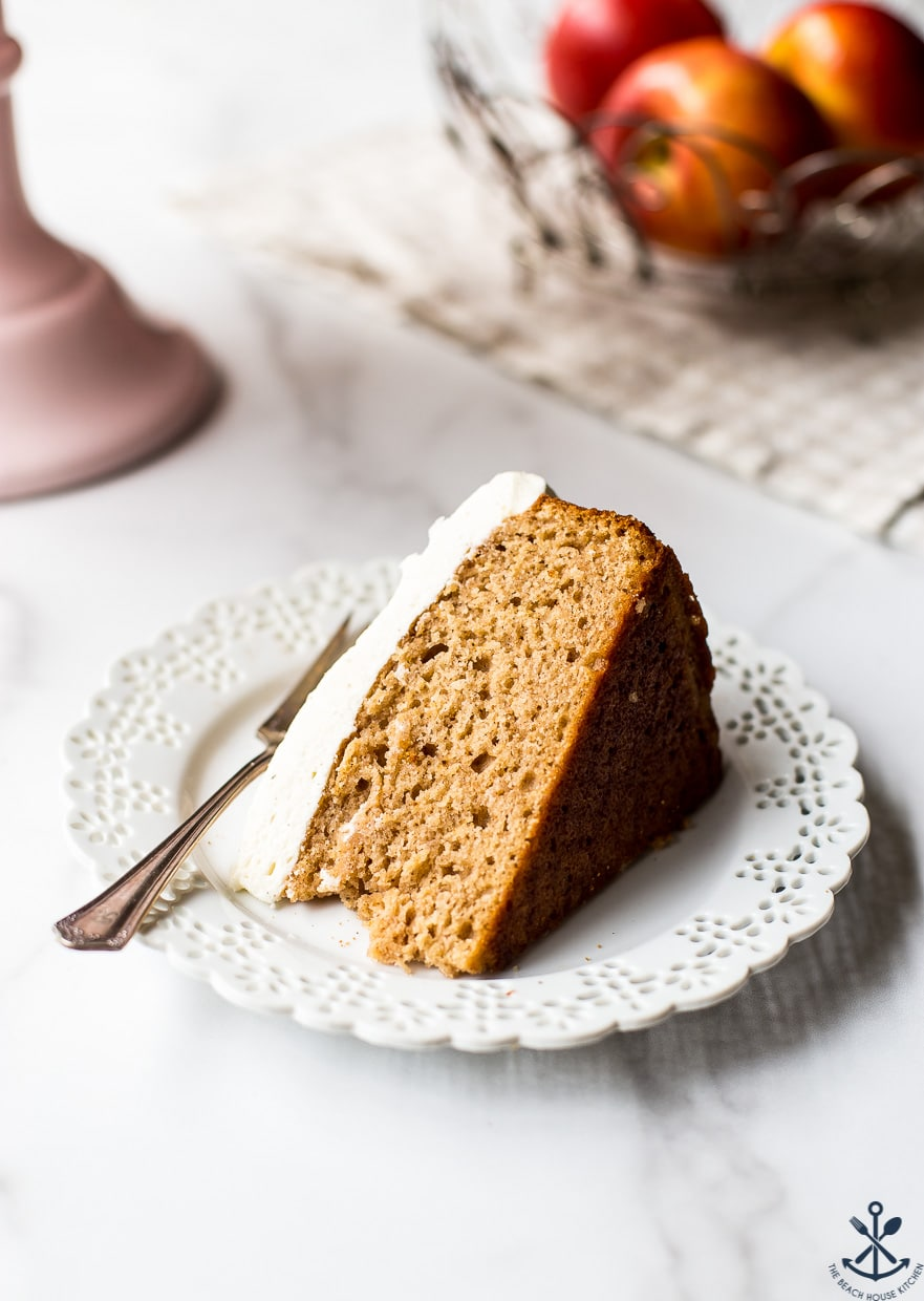 Up close photo of a slice of applesauce cake with vanilla bean frosting on a plate