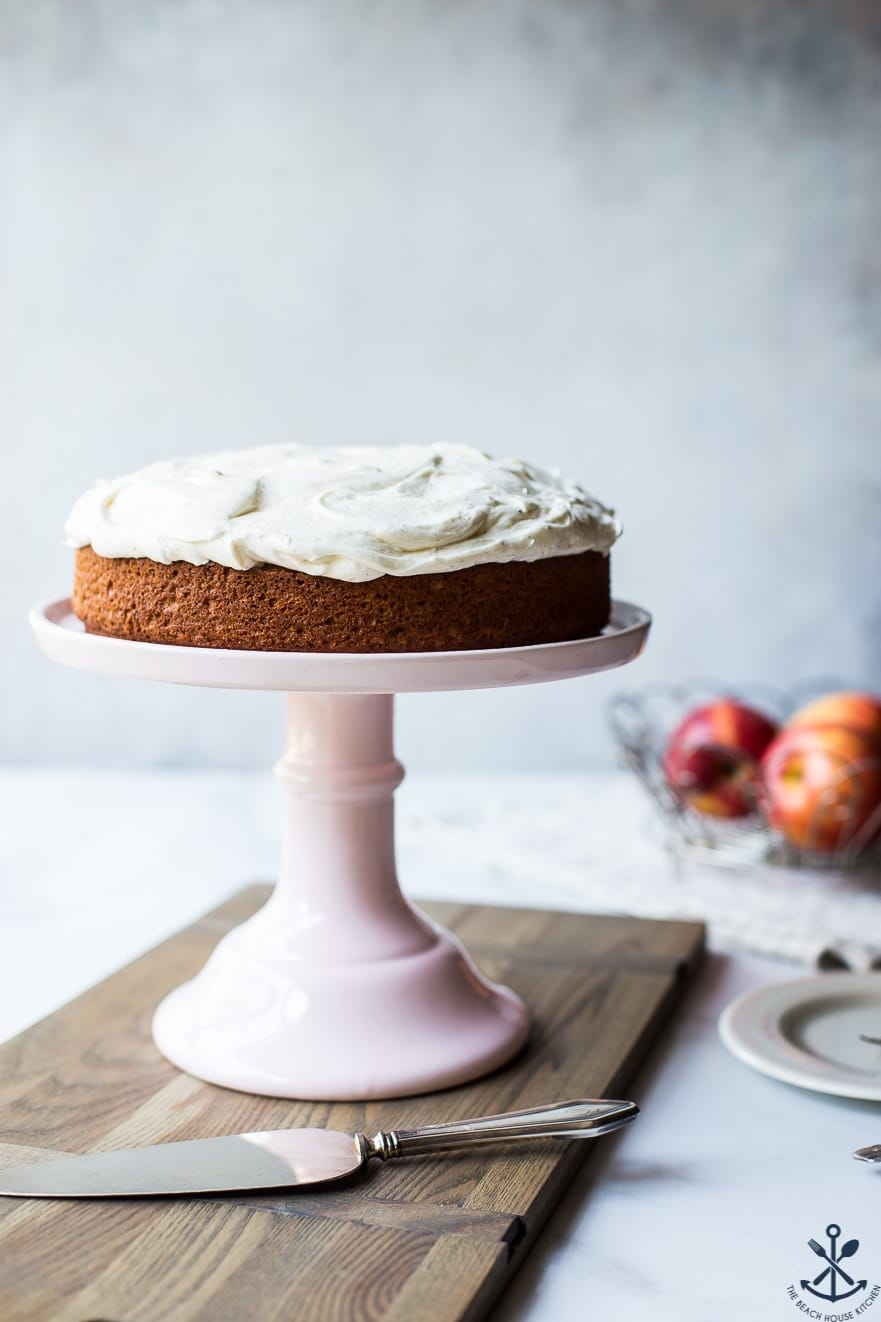 Applesauce cake with vanilla bean frosting on a pink cakestand