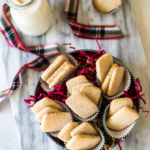 Overhead photo of biscochitos cookies in a round cookie tin