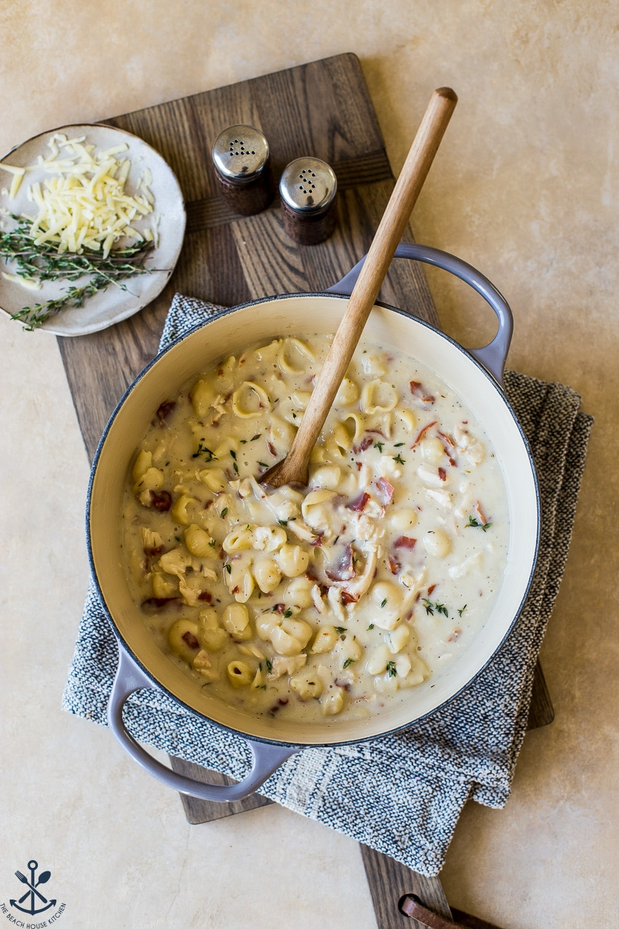 Overhead photo of pasta in a pot with a wooden spoon
