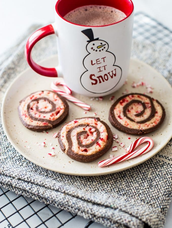 Chocolate peppermint pinwheel cookies on a plate with a mug of hot cocoa