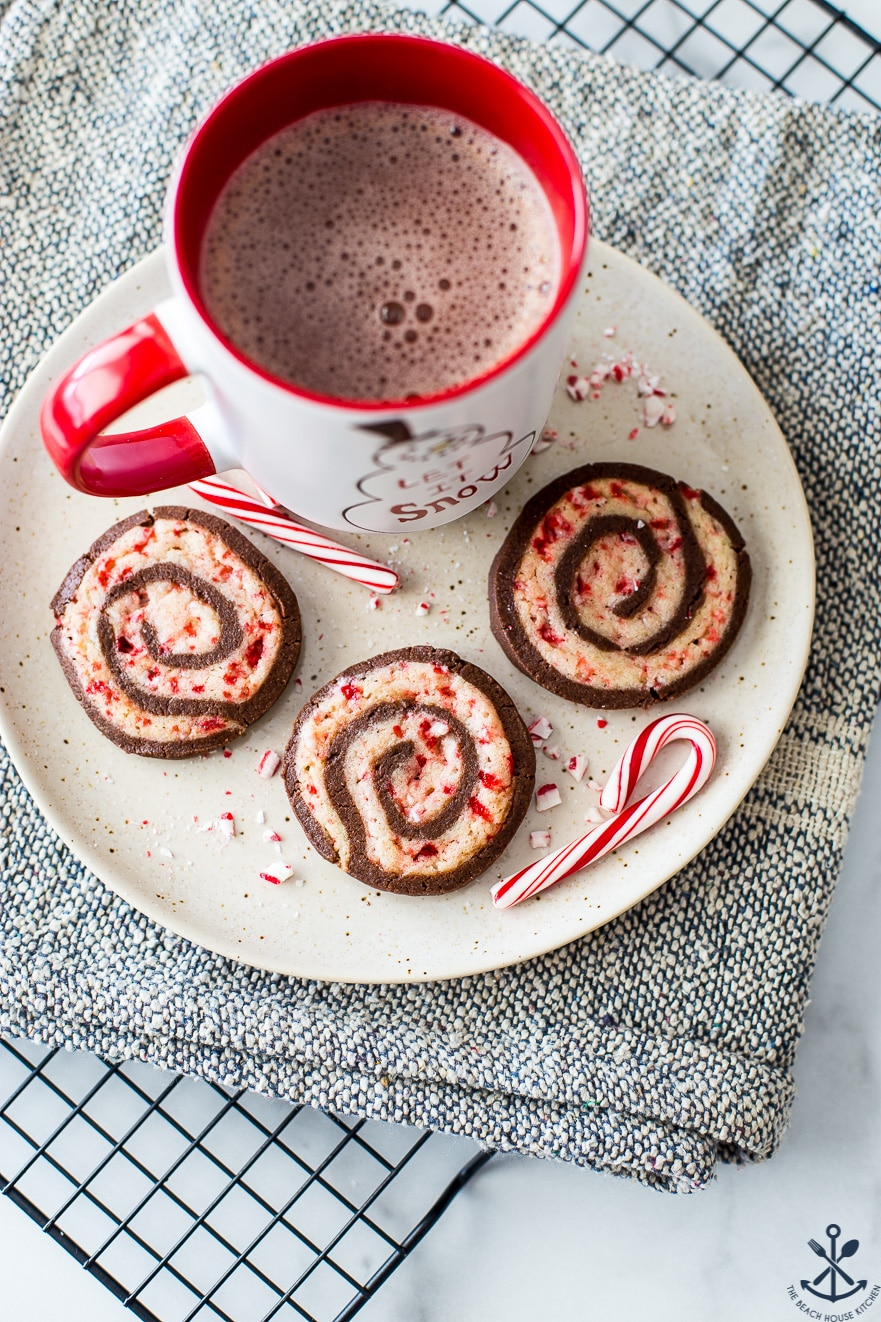 Overhead photo of chocolate peppermint pinwheel cookies on a plate with a mug of hot cocoa