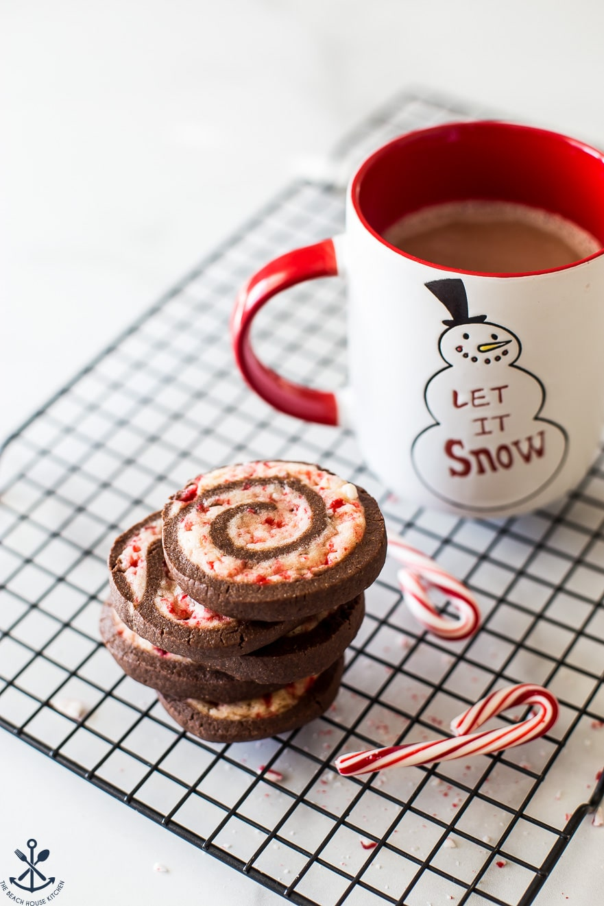 A stack of chocolate peppermint pinwheel cookies on a plate with a mug of hot cocoa