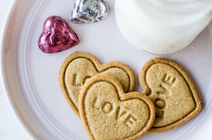 Overhead photo of 3 heart shaped cookies imprinted with LOVE on a plate with a bottle of milk