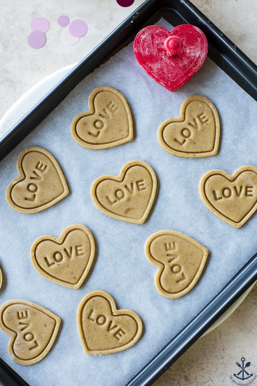 Overhead photo of pre-baked heart cookies imprinted with LOVE