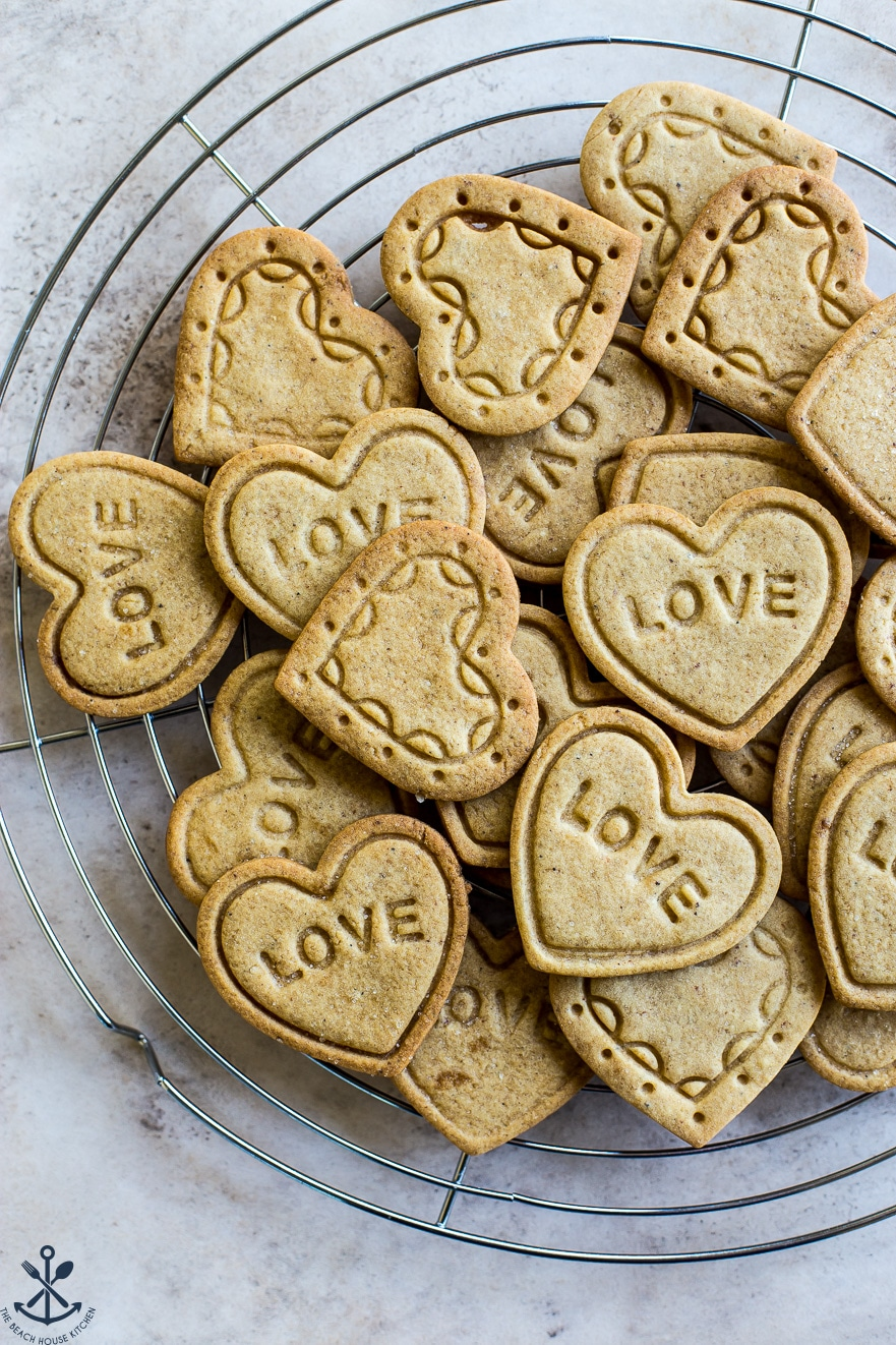 Overhead photo of heart cookies imprinted with designs and LOVE on a silver wire rack