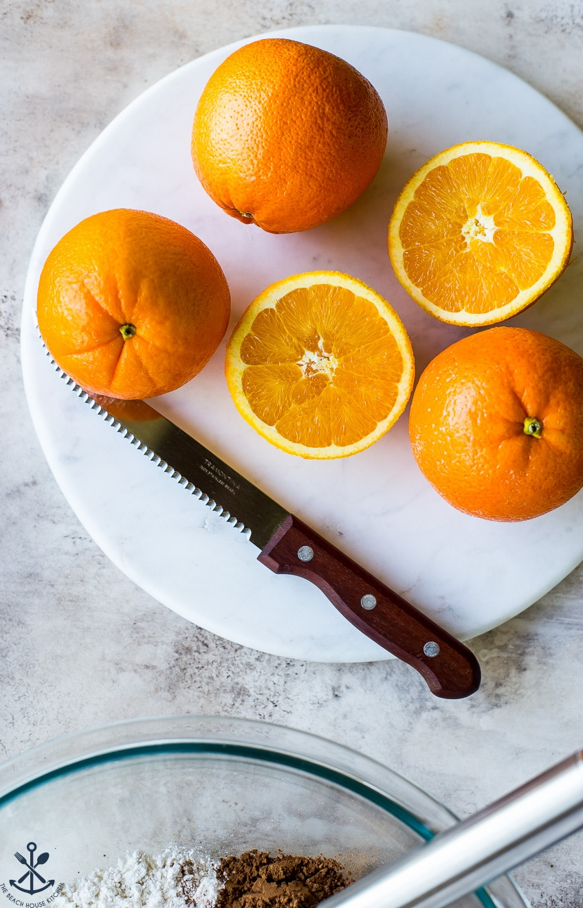 Oranges on a marble circular board with a sharp knife with a wooden handle.