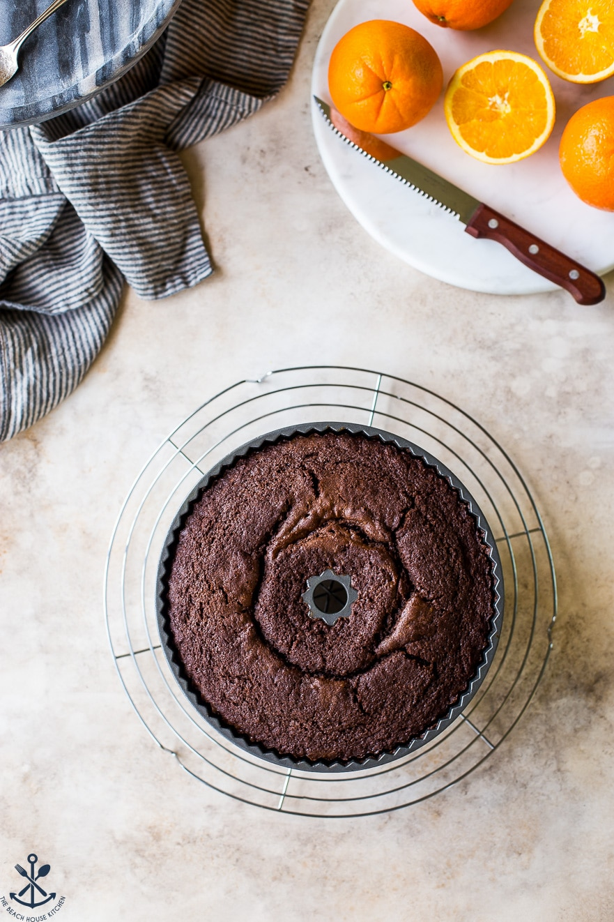 An overhead photo of a baked chocolate orange bundt cake in the pan on a wire rack.