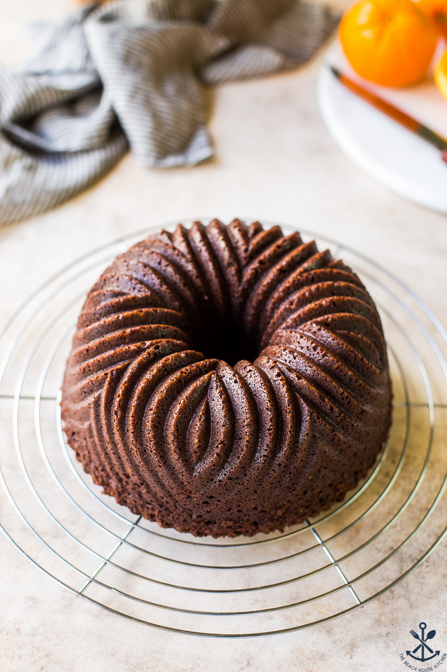 Chocolate Orange Bundt Cake on a round silver wire rack.
