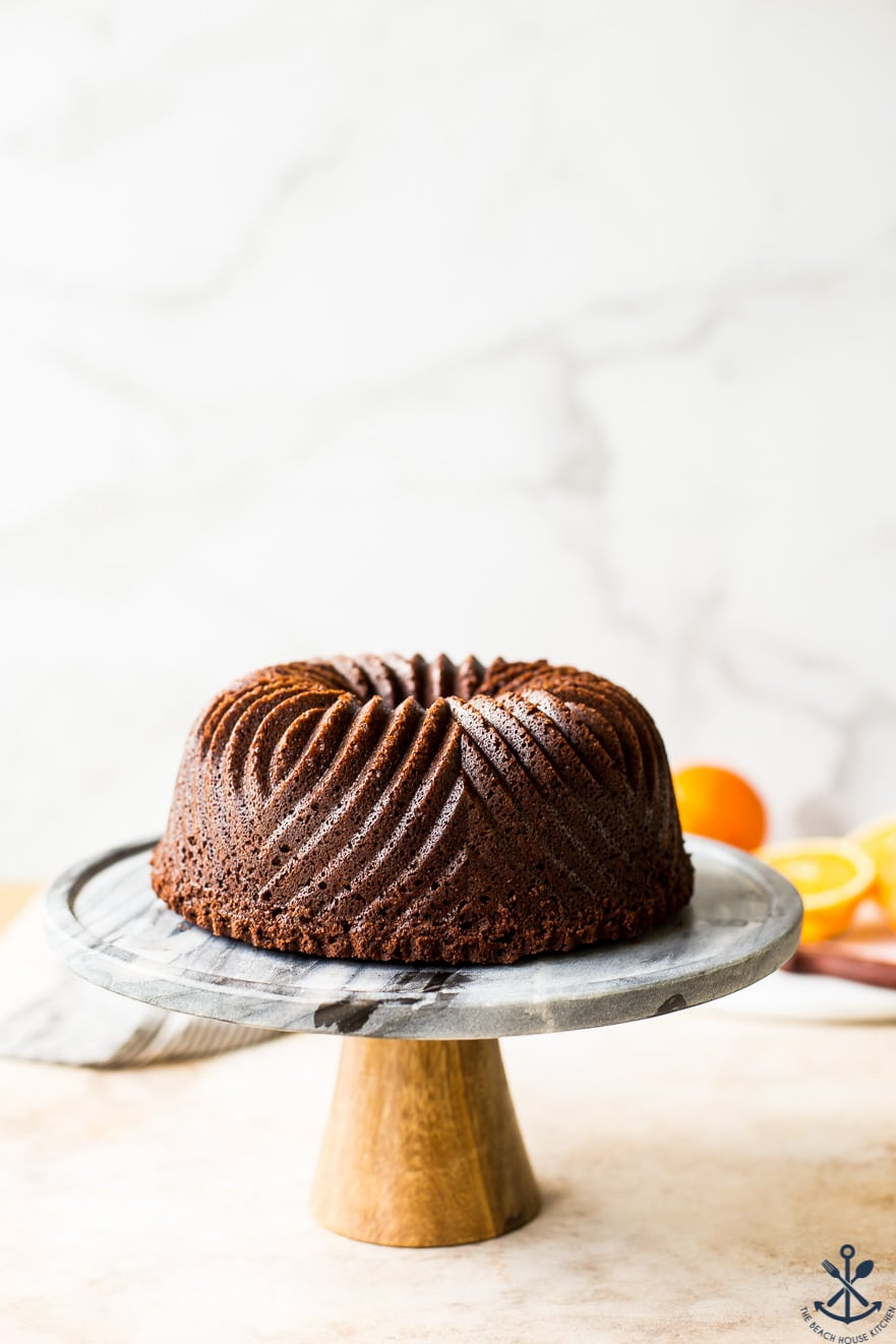 A chocolate orange bundt cake on a a cake stand with a wooden base.