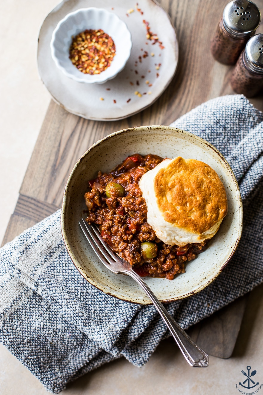 Overhead photo of bowl filled with Cuban Beef Picadillo topped with a biscuit