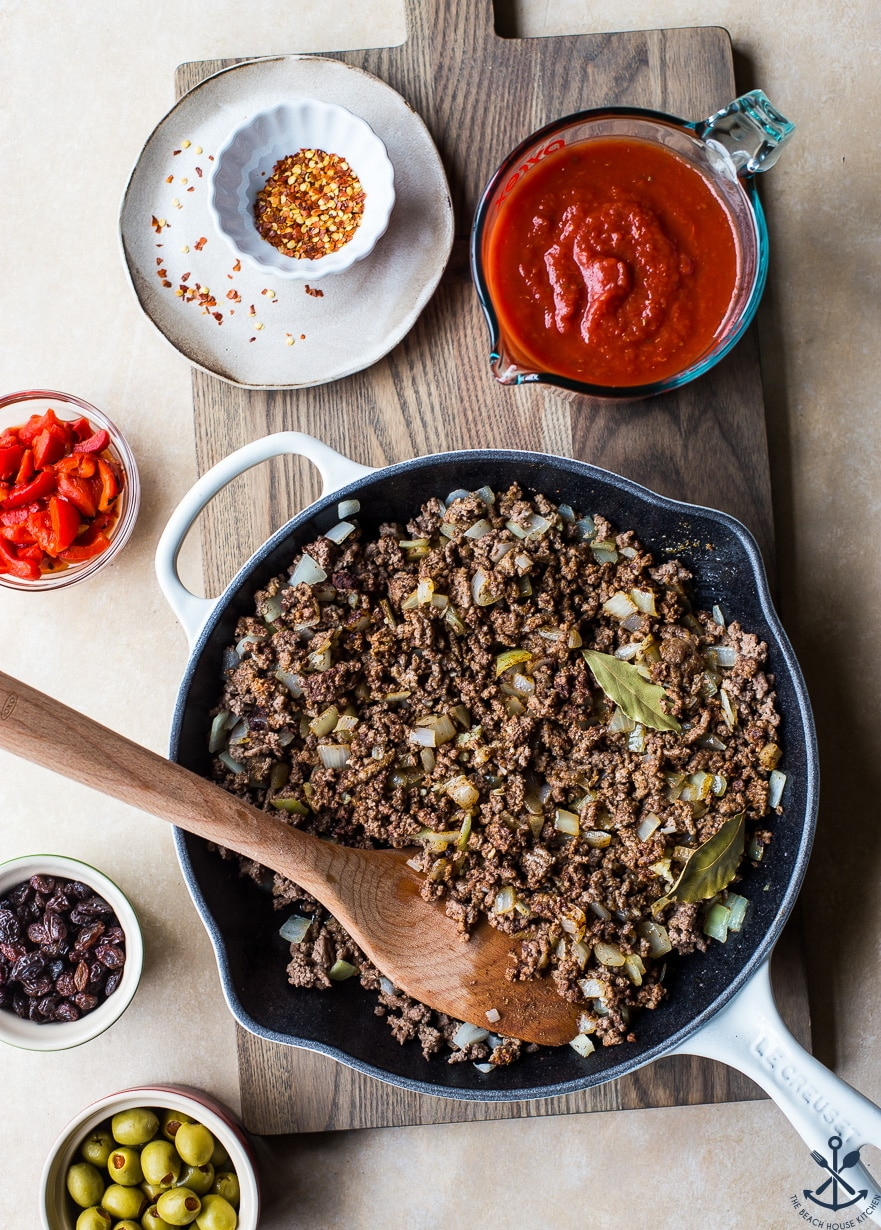 Overhead photo of ground beef in skillet for Cuban beef picadillo