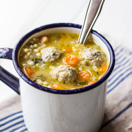 Italian Wedding Soup in a mig with a spoon