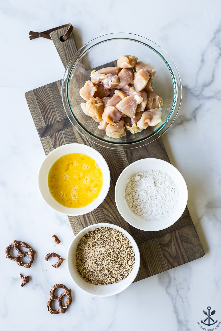 Ingredients for pretzel crusted chicken nuggets in bowls