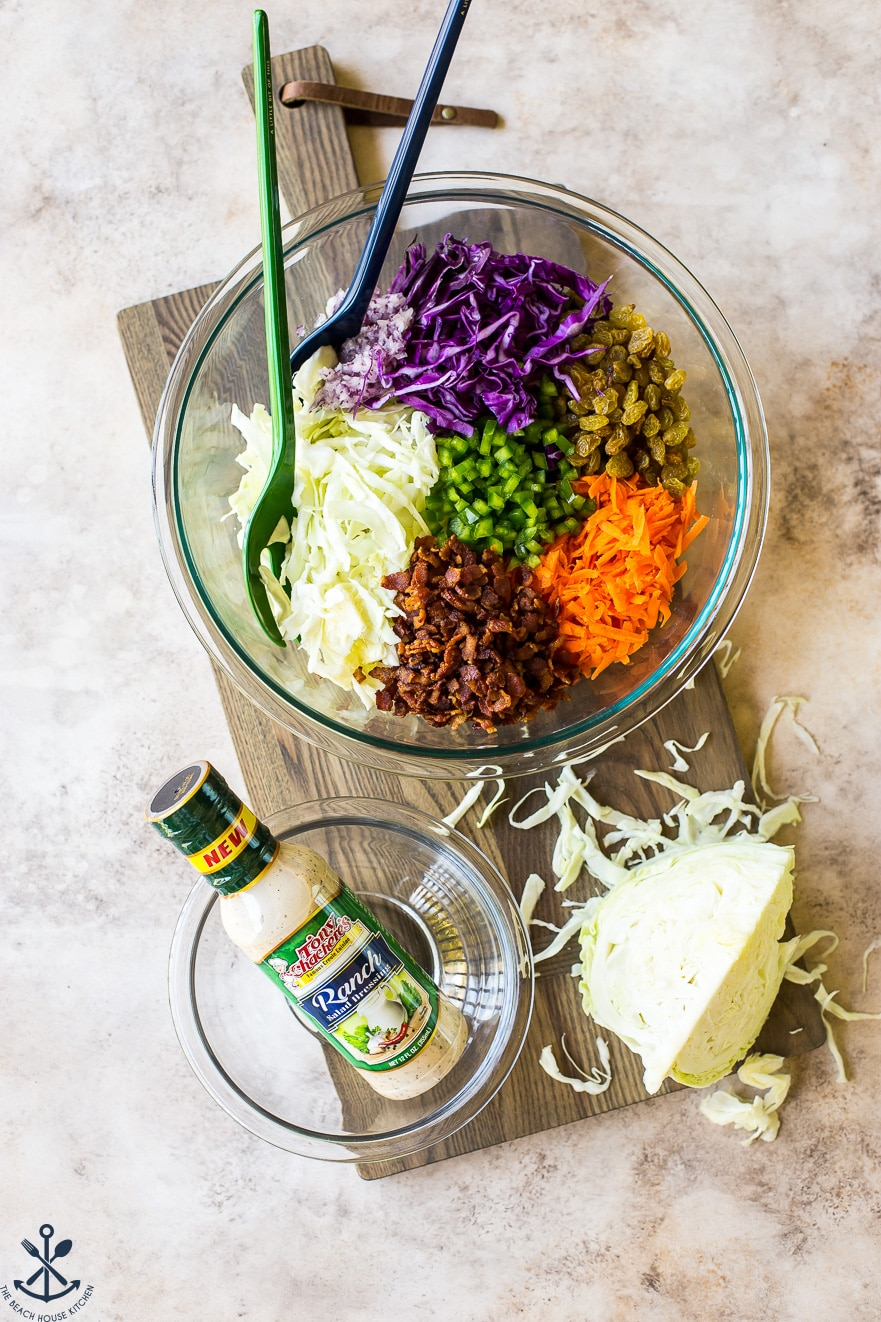 Overhead photo of ingredients for bacon ranch cole slaw in a glass bowl
