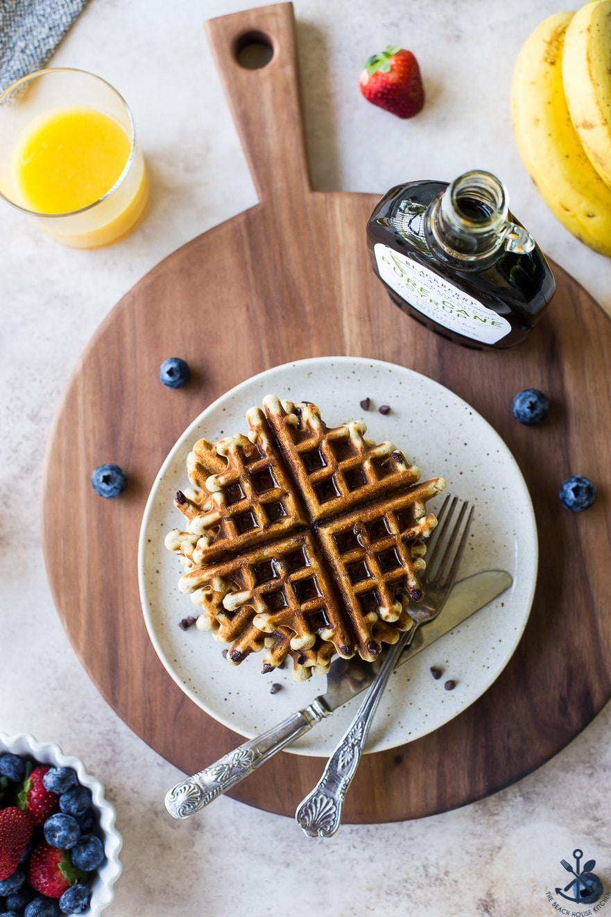 Overhead photo of chocolate chip banana bread waffles on a plate on a wooden board