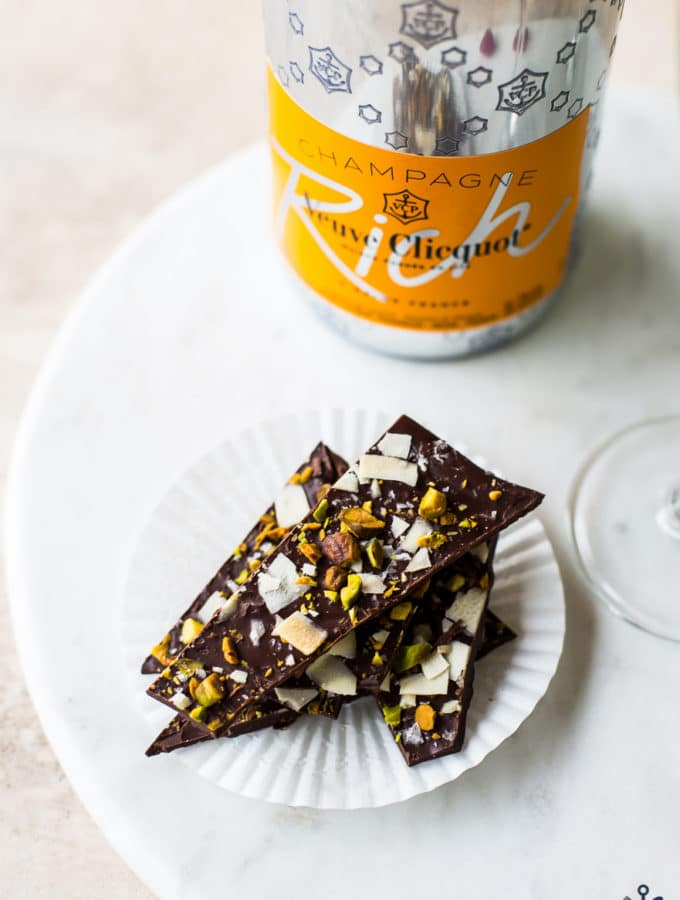 Chocolate coconut pistachio bark on a round marble board with a bottle of champagne