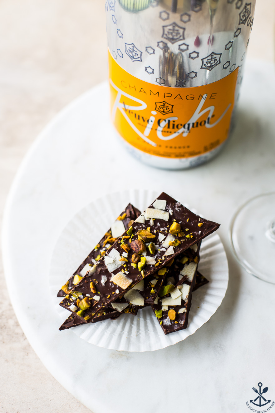 Overhead photo of chocolate coconut pistachio bark and a bottle of champagne