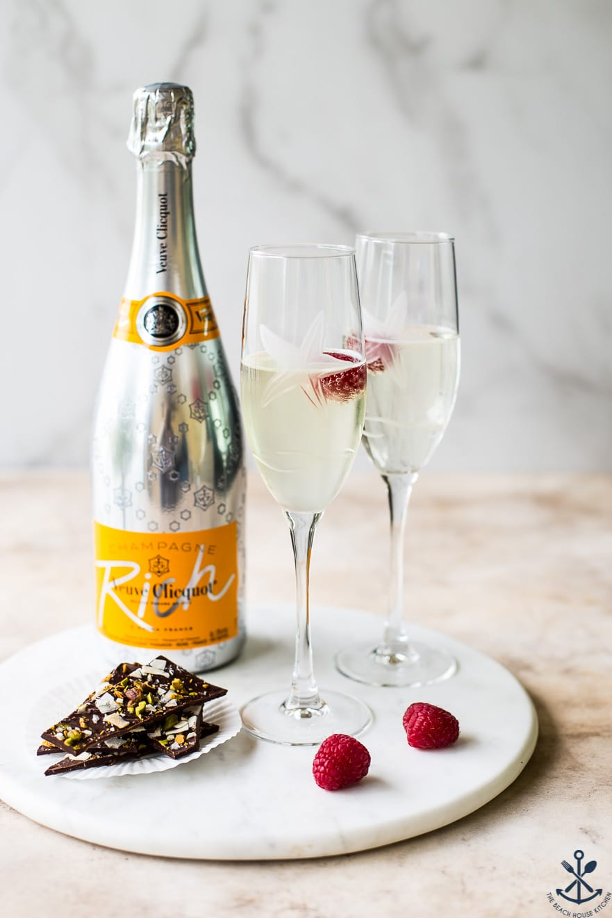 A round marble board with a bottle of champagne, two champagne glasses, raspberries and chocolate coconut pistachio bark