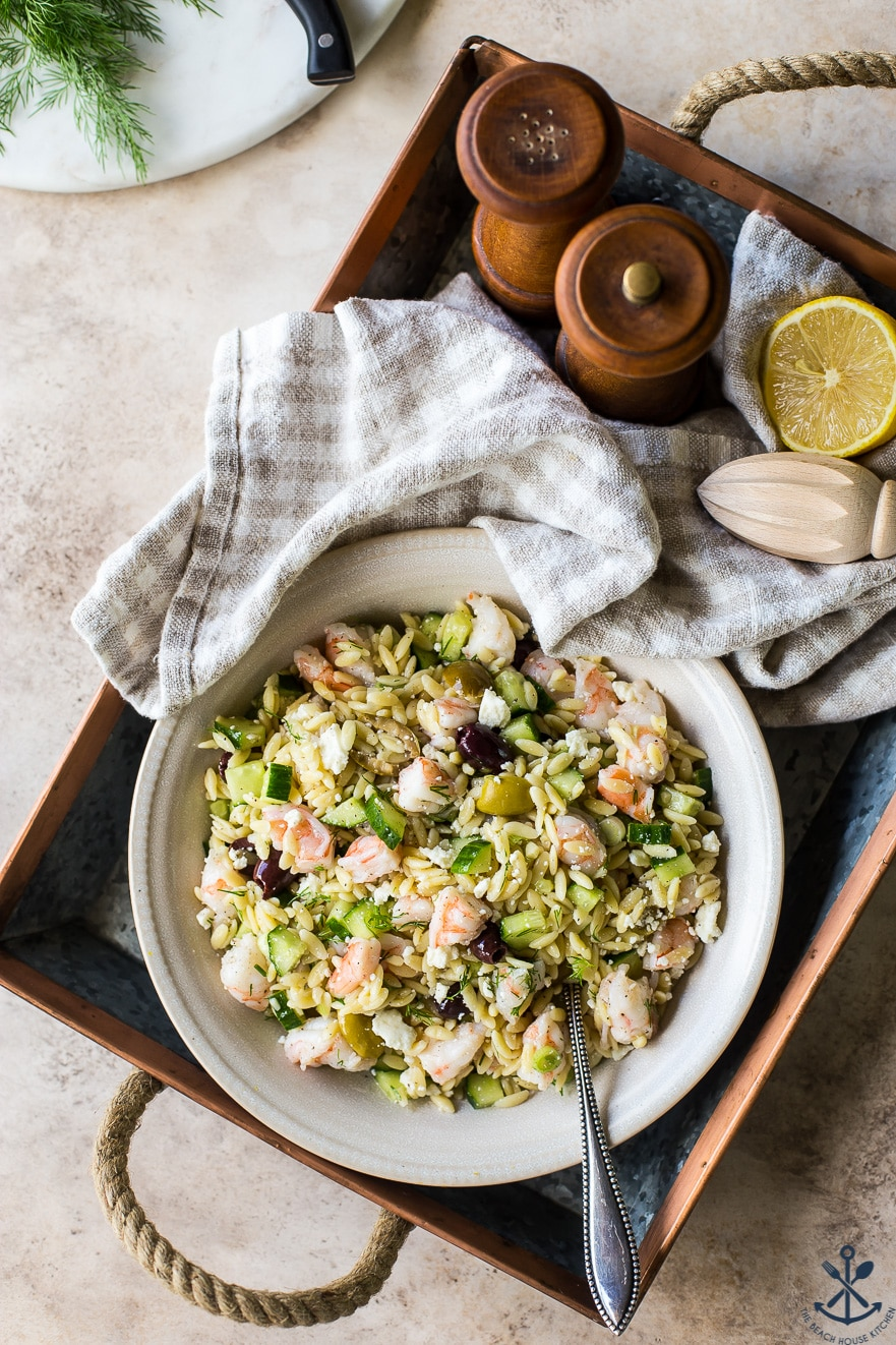 Overhead photo of lemony orzo pasta salad in a cream colored bowl in a silver tray