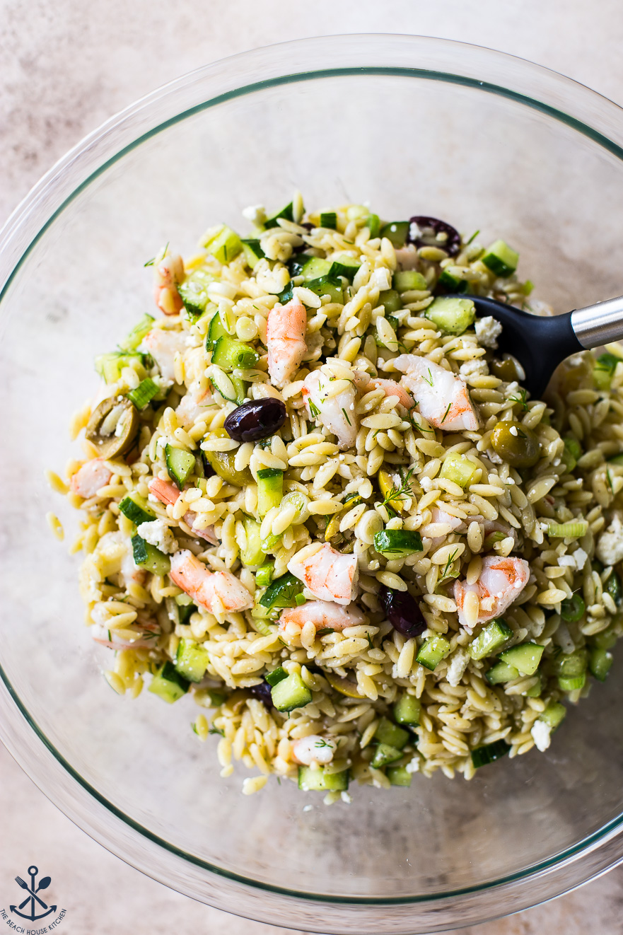 Overhead photo of glass bowl filled with lemony orzo pasta salad with shrimp