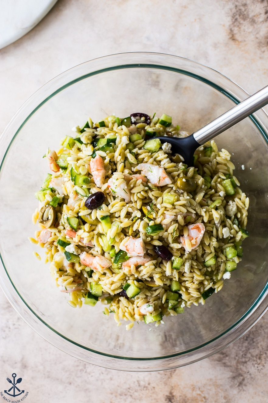 Overhead photo of lemony orzo pasta salad with shrimp in glass bowl