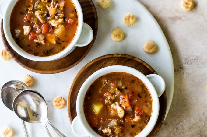 Overhead photo of two white bowls filled with manhattan clam chowder on a round marble board with three spoons